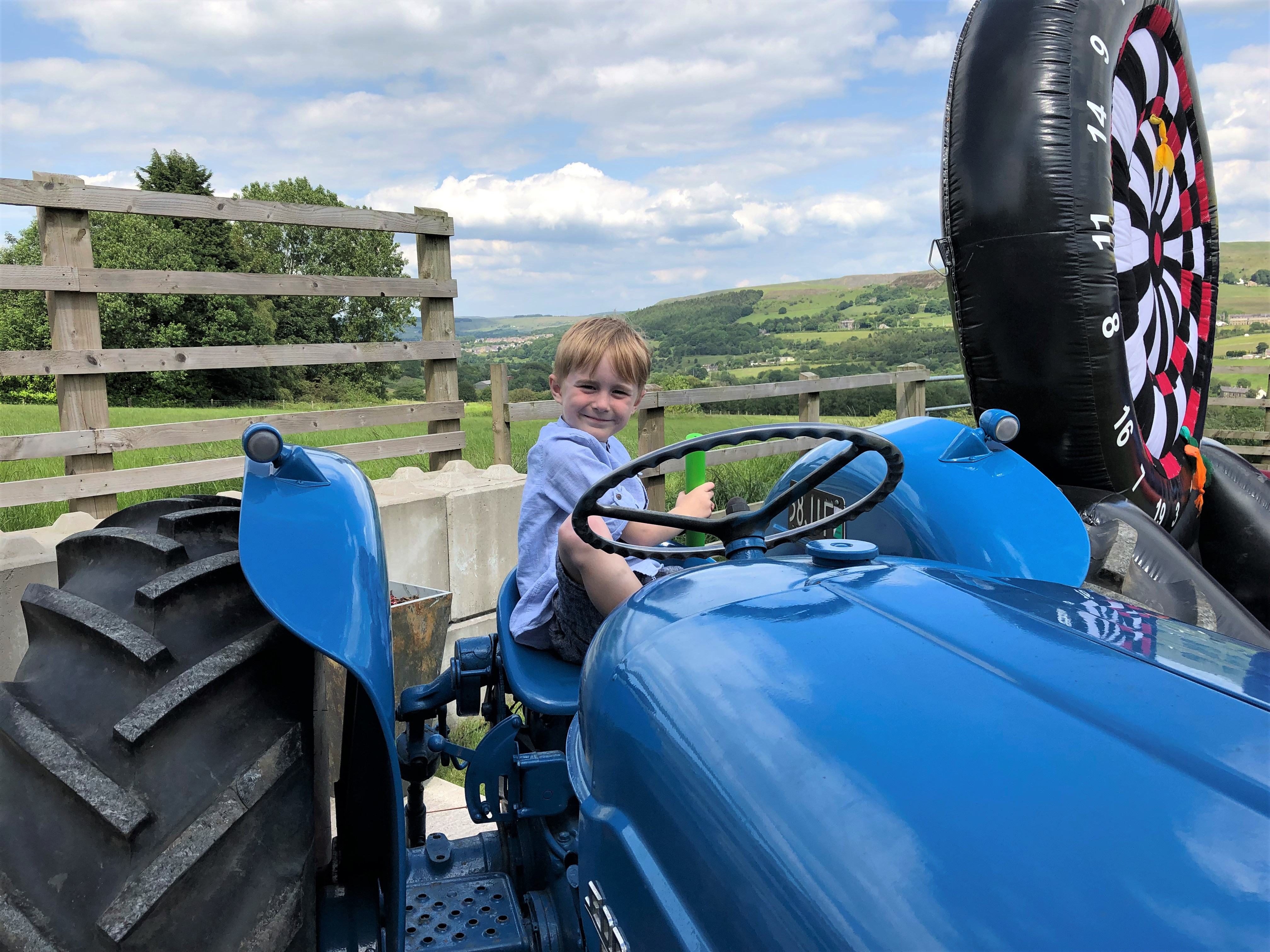 Child sitting on blue tractor